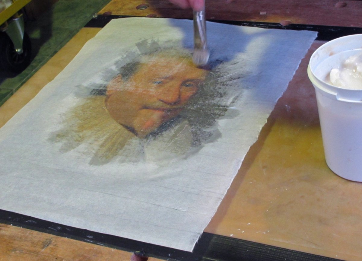 The painting is protected by glueing a thick paper. The glue is applied from the center to the edges to get rid of the air bubbles